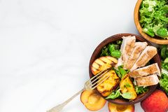 Salad with grilled chicken and peach in a bowl with fork. healthy food. top view