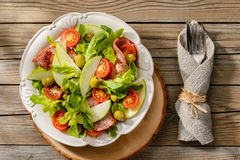 Salad with grilled ham, tomatoes, apples and green olives. Fresh salad with grilled ham, tomatoes, apples and green olives on placemat on wooden table Stock Photos