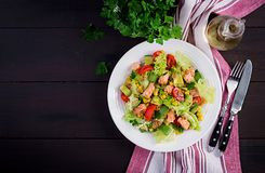 Salad with grilled salmon, lettuce, avocado, tomatoes and corn on a white bowl