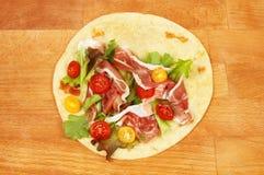 Salad and ham on flatbread. Salad and parma ham on a piada flatbread royalty free stock image