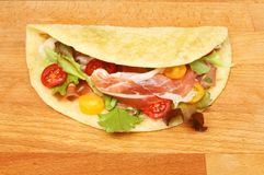 Salad and ham piada. On a wooden chopping board Royalty Free Stock Photo