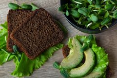 Salad healthy sandwiches made from black unleavened rye bread with ripe avocado and fresh pea sprouts. royalty free stock photos