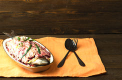 Salad herring under a fur coat on a wooden table in the backgro Royalty Free Stock Photos
