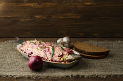 Salad herring under a fur coat on a wooden table in the backgro Stock Photo