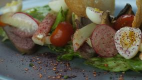 Salad with an iceberg, boiled veal tongue, quail eggs, radish and marinated mushrooms, decorated with two slices of. Bread crumbs of white bread sprinkled with stock video footage