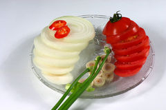 Salad ingredients. Sliced onions, tomato, lemon grass and spring onions on a glass dish Stock Images