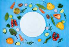 Salad ingredients around empty white plate on light blue grunge. Background, top view, frame. Health salad making royalty free stock image