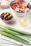 Salad ingredients. For greek salad olives olive oil tomato gherkins feta soft cheese chive green onion Stock Images