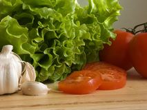 Salad ingredients II. Garlic, salad and sliced tomatoes on a wooden chopping board Stock Photos