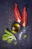 Salad ingredients: red pepper, lettuce, olive oil on rustic wooden background. Fresh vegetables, top view. Stock Photos