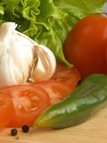 Salad ingredients VII. Garlic, chilli, salad and sliced tomatoes on a wooden chopping board Royalty Free Stock Images