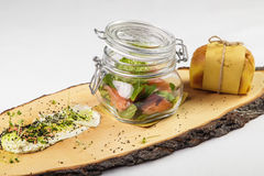 Salad in jar with sauce and small bun on wooden board on white b stock photography