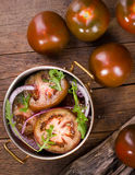 Salad of kumato tomatoes. Salad with kumato tomatos, red onions and rucola Stock Photos