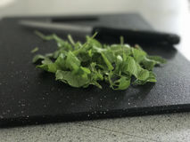 Salad leaves on chopping board. Salad leaves on a granite style chopping board with blurry knife in background Stock Photos