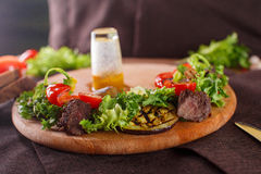 Salad leaves with sliced roast beef and sun-dried cherry tomatoes. On wooden background Stock Images