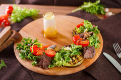 Salad leaves with sliced roast beef and sun-dried cherry tomatoes. On wooden background Royalty Free Stock Image