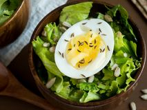 Salad of lettuce leaves and eggs in wooden bowls seeds cumin loaves Dark background.  Royalty Free Stock Photo