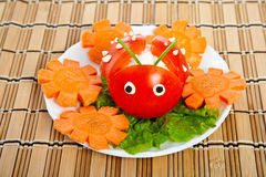 Salad from lettuce and tomato in form ladybird. Royalty Free Stock Photo