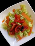 Salad of lettuce and tomato on white tray. And blach bacground Stock Images