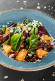 Salad with liver, arugula, orange, spinach and almonds on plate over dark stone surface. Healthy food concept. Top view.  royalty free stock photo