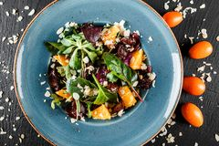 Salad with liver, arugula, orange, spinach and almonds on plate over dark stone surface. Healthy food concept. Top view.  stock photography