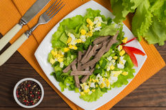 Salad with liver, eggs, lettuce and green onions. Wooden background. Top view. Close-up Royalty Free Stock Images