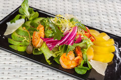 Salad with mango and shrimp on a light background Stock Photos