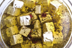 Salad marinated cheese. Cheese cubes marinated in olive oil with herbs stock photo