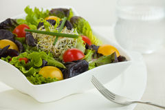Salad meal time. Mixed green salad meal in a white bowl with fork and glass of water, Shallow depth of field Stock Photo