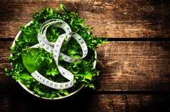 Salad and measuring tape on rustic wooden background.  Diet Food Stock Photography