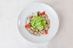 Salad with meat in a creamy sauce, ase, lettuce, romaine, iceberg cherry tomatoes on top of the plate  Royalty Free Stock Photos