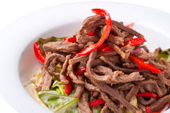 Salad of meat with red pepper on white plate. Close up Stock Image