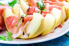 Salad of melon with thin slices of prosciutto, arugula leaves and balsamic sauce closeup Stock Photo