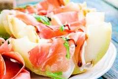 Salad of melon with thin slices of prosciutto, arugula leaves and balsamic sauce closeup Royalty Free Stock Photo