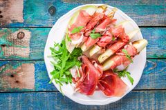 Salad of melon with thin slices of prosciutto, arugula leaves and balsamic sauce top view stock photo