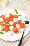 Salad with mini mozzarella, tomatoes and fresh basil on a plate Stock Photo