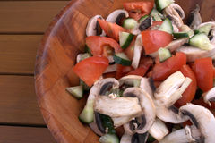 Salad in the mix. Wooden salad bowl with mushrooms tomatoes and cucumber Royalty Free Stock Photos