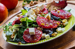 Salad: mix of green salad, feta cheese, red oranges and walnuts. Dressing: olive oil. Selective focus Stock Photos