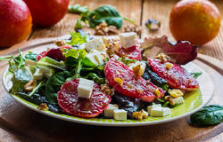 Salad: mix of green salad, feta cheese, red oranges and walnuts. Dressing: olive oil. Selective focus Royalty Free Stock Photos