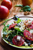 Salad: mix of green salad, feta cheese, red oranges and walnuts. Dressing: olive oil. Selective focus Royalty Free Stock Photo