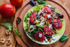 Salad: mix of green salad, feta cheese, red oranges and walnuts. Dressing: olive oil. Selective focus, top view Stock Photography