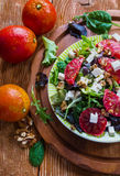 Salad: mix of green salad, feta cheese, red oranges and walnuts. Dressing: olive oil. Selective focus, top view Royalty Free Stock Photography