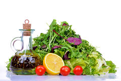 Salad mix with rucola, frisee, radicchio, lettuce and bottle of olive oil, lemon. Tomatoes stock photo