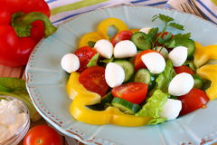 Salad with mozzarella and fresh vegetables on wooden table background. Stock Photo