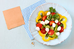 Salad with mozzarella and fresh vegetables on wooden table background. top view. Royalty Free Stock Photo