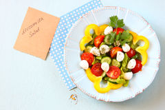 Salad with mozzarella and fresh vegetables on wooden table background. top view. Royalty Free Stock Photos