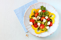 Salad with mozzarella and fresh vegetables on wooden table background. top view. Stock Photography