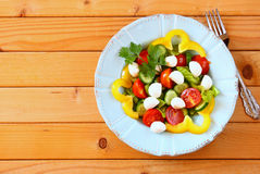Salad with mozzarella and fresh vegetables on wooden table background. top view. Stock Photo