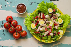 Salad with mushrooms, chicken, quail eggs, paprika, lettuce and pomegranate, on a old table. Top view Royalty Free Stock Photography