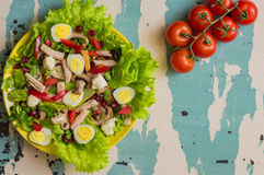 Salad with mushrooms, chicken, quail eggs, paprika, lettuce and pomegranate, on a old table. Top view Royalty Free Stock Photos